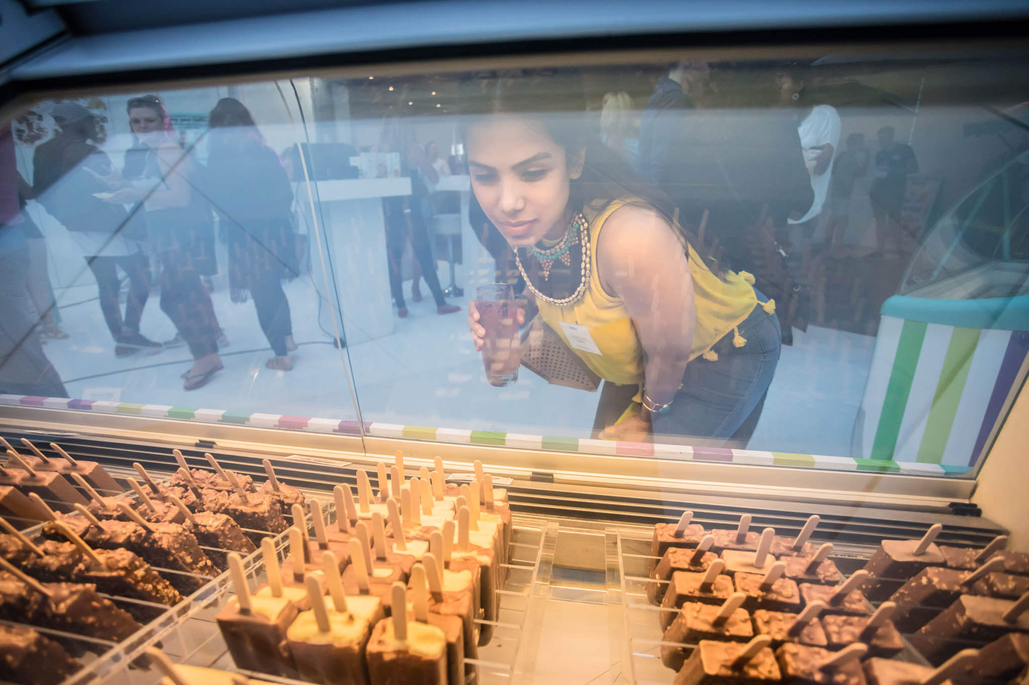Young lady looking at Ice Cream through the display glass